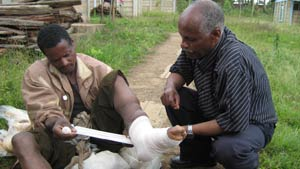 A man being shown how to bandage his feet